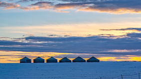 Wheat Storage Bins in a Snowy Dusk. Like silent sentinels a row of wheat storage bins wait for the sunset on a cold ridge in the high desert of central Oregon Stock Photo