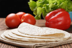 Wheat tortillas with vegetables on old wooden table Royalty Free Stock Photos