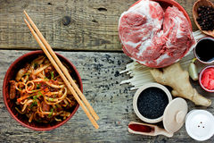 Wheat udon noodles with fried pork meat and sauce. Prepared dish and ingredients for cooking, recipe of traditional Asian cuisine top view Royalty Free Stock Photos