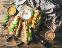 Wheat unfiltered beer and grilled sausage dogs in baguette Royalty Free Stock Image