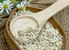 Wheaten flakes. Crude flakes in wooden spoon, cones and camomiles Royalty Free Stock Photography