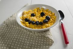Wheaties cereal and blueberry in bowl with table cloth and spoon. On white background Stock Images