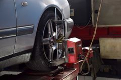 Wheel alignment in garage. Tire clamped with aligner auto wheel alignment in garage Royalty Free Stock Images