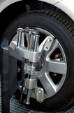 Wheel Alignment Machine Clamp. Car wheel fixed with computerized wheel alignment machine clamp. Closeup of repairshop equipment stock image