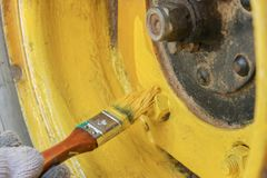The wheel of the all-terrain vehicle is painted in yellow with a brush. The process of painting the wheel with a brush in yellow color with yellow paint stock photos