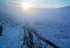 Free Wheel And Human Track On Snow Covered Mountain Road Royalty Free Stock Photography - 164794427