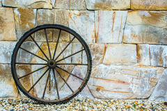 Wheel. Antique metal wheel rests on a wall of stones Royalty Free Stock Images