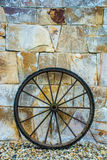 Wheel. Antique metal wheel rests on a wall of stones Royalty Free Stock Image