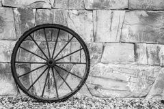 Wheel. Antique metl wheel rests on a wall of stones Royalty Free Stock Photography