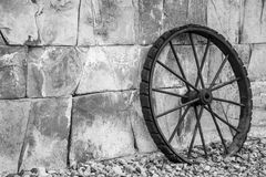 Wheel. Antique metl wheel rests on a wall of stones Stock Image
