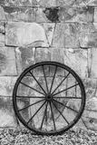 Wheel. Antique metl wheel rests on a wall of stones Stock Photography