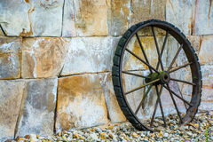 Wheel. Antique wheel rests on a wall of stones Stock Image