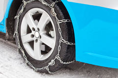 Wheel with antiskid iron chain. The wheel with antiskid iron chain runs on the ice/snow cover road, to keep safe and avoid trackslip when driving Royalty Free Stock Photo