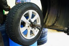 Wheel balancing or repair and change car tire at auto service garage or workshop by mechanic. Toned Stock Photo
