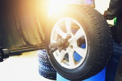 Wheel balancing or repair and change car tire at auto service garage or workshop by mechanic. Toned Royalty Free Stock Image