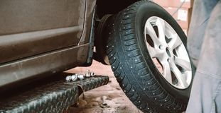 Wheel balancing or repair and change car tire at auto service garage or workshop by mechanic. Toned Stock Photos