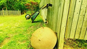 Wheel Barrel and hanging ladder along the  fence  side Royalty Free Stock Photos