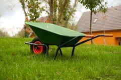 Wheel barrow. Green wheel barrow on the grass in the garden royalty free stock photo