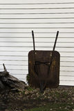 Wheel Barrow. An old wheel barrow leaning against a wall Royalty Free Stock Image