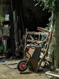 Wheel barrow at rest. Rusty wheel barrow leant against old gate in yard Stock Photography