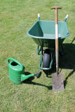 Wheel barrow, shovel, spade and watering can in the garden Stock Image