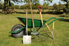 Wheel barrow and tools. Photograph of a wheel barrow and garden tools shot in garden Royalty Free Stock Image