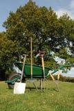 Wheel barrow and tools. Photograph of a wheel barrow and garden tools shot in garden Stock Image