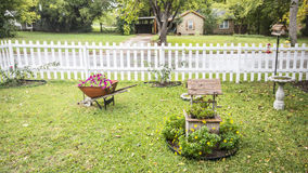 Wheel Barrow and Wishing Well with Flora. My Front yard with wheel barrow filled with red flowers and a wishing well with yellow flower alontg with rose bushes Stock Image