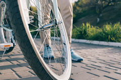Wheel of a bicycle and female feet in sneakers Stock Images