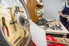 Wheel and bicycle parts over workshop table Stock Photography
