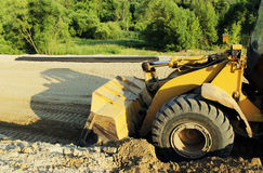 Wheel bulldozer machine for shoveling sand at eathmoving works in construction site. On a road Stock Photos