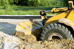 Wheel bulldozer machine for shoveling sand at eathmoving works in construction site. On a road Royalty Free Stock Images