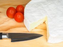 Camembert cheese on board with knife. Wheel of Camembert cheese on cutting board with knife and whole cherry tomatoes Royalty Free Stock Photography