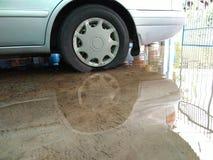 Wheel of car soaks in water. Car parking in garage, wheel soaks in water on the floor Stock Photo