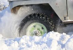 The wheel of the car is stuck in the snow. spray of snow from the rotating wheel of winter tires. slipping machine in the snow. th. Wheel of  car is stuck in Stock Photos
