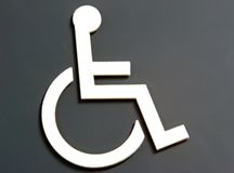 Wheel Chair Access. Universal wheelchair access symbol on a sign. White on Gray Royalty Free Stock Image
