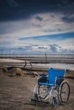 Wheel chair at the beach Royalty Free Stock Photos