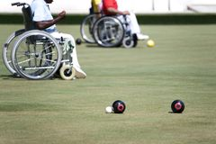 Wheel Chair Lawn Bowls for Disabled Persons (Men). Wheel chair lawn bowlers in action in an international competition Stock Photo