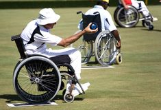 Wheel Chair Lawn Bowls for Disabled Persons (Men). Wheel chair lawn bowlers in action in an international competition stock image