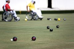 Wheel Chair Lawn Bowls for Disabled Persons (Men). Wheel chair lawn bowlers in action in an international competition royalty free stock photography