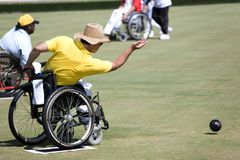 Wheel Chair Lawn Bowls for Disabled Persons (Men). Wheel chair lawn bowlers in action in an international competition stock images