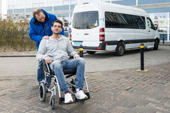 Wheel chair taxi. Disabled men in a wheel chair and his male nurse being dropped off at a hospital by a wheel chair taxi royalty free stock images