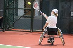 Wheel Chair Tennis for Disabled Persons (Women). A wheel chair tennis player in action in an international tournament royalty free stock photos