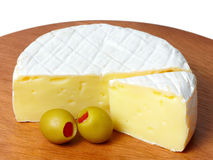 Wheel of cheese with green olives. Stock Photos