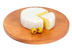 Wheel of cheese with green olives. Royalty Free Stock Image