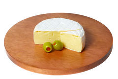 Wheel of cheese with green olives. Royalty Free Stock Photos