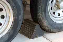 Wheel chock and tires. A wheel chock is between two old tires on a trailer. Prevents vehicle from rolling away Stock Images