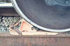 Wheel chock under the train wheel on the rails, close-up royalty free stock photography