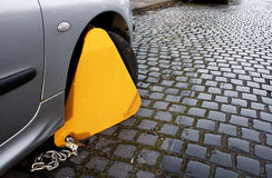 Wheel clamping. Car with clamp on to immobilize movement as a penalty to an offence such as no tax Royalty Free Stock Images