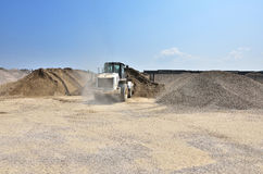 Wheel dozer at work on site. Gravel and sand materials for manufacturing the cement and asphalt. Big white wheel dozer load the materials for manufacturing the stock image